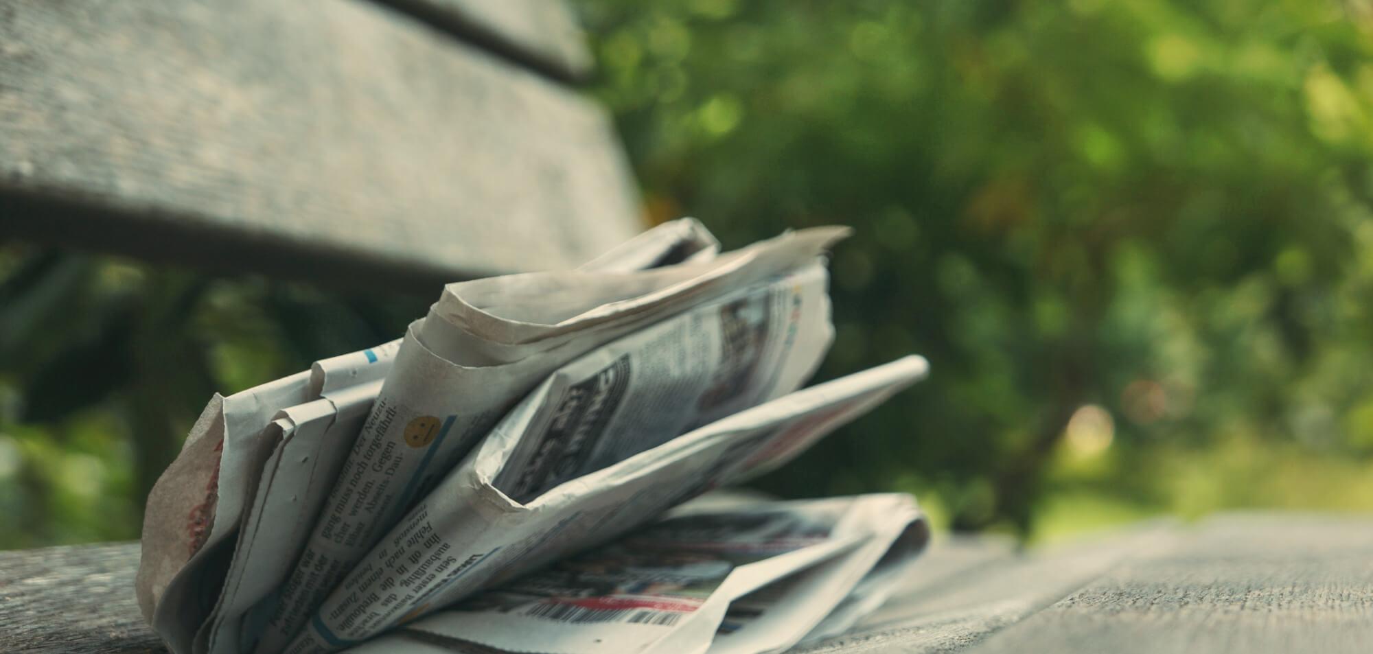 Tidning på en bänk i skogen