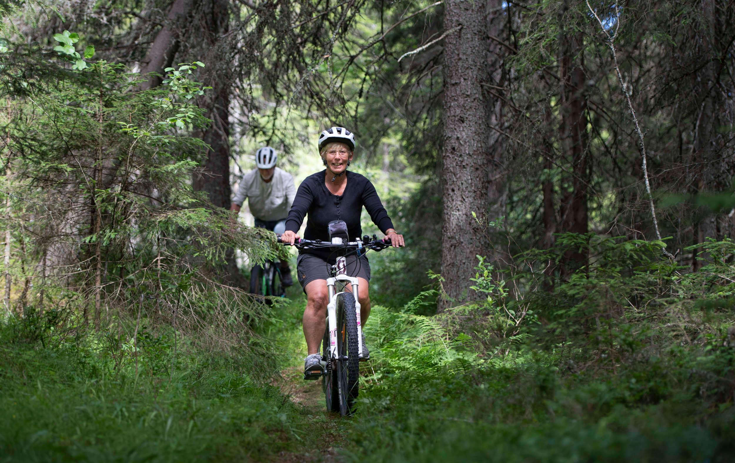 Två personer cyklar i skogen