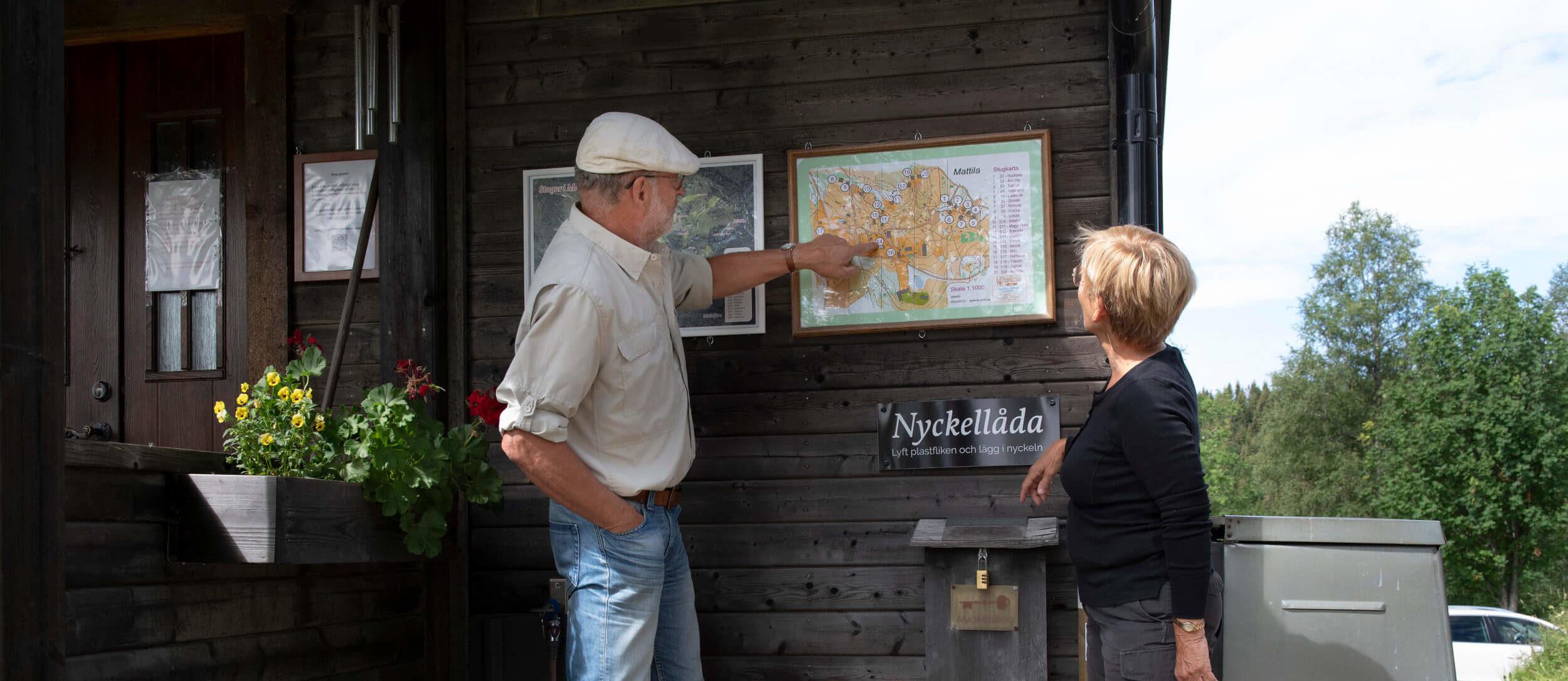Två personer pekar en karta på väggen