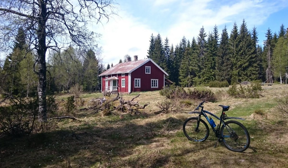 Cykel med ett rött hus i bakgrunden