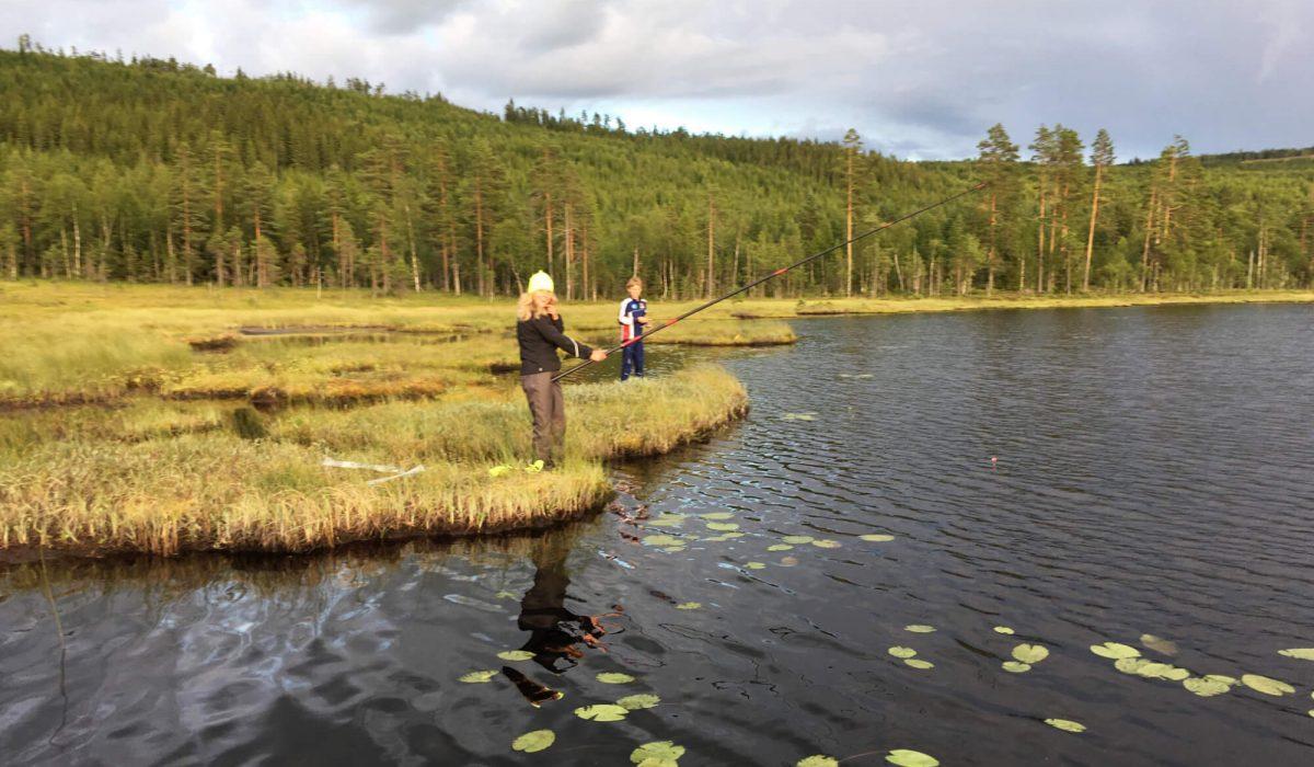 Två personer fiskar i en sjö