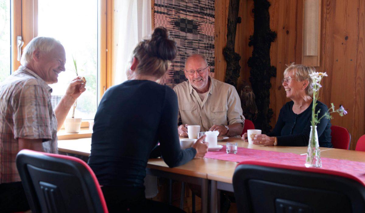 Personer sitter och äter vid ett bord